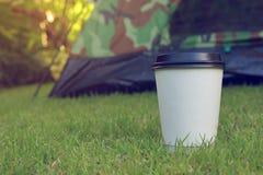 热的咖啡饮料,在绿草的白色一次性杯子 库存图片