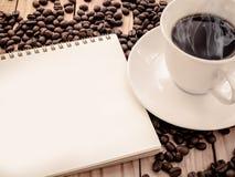 热的咖啡,与空白的笔记本的咖啡豆 免版税库存图片