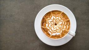 热的在具体桌上的咖啡热奶咖啡拿铁艺术顶视图顶视图  免版税库存照片