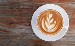 热的在木背景的咖啡热奶咖啡拿铁艺术顶视图 库存照片