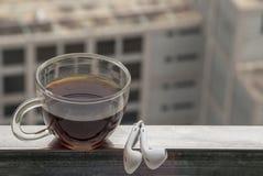热的在阳台安置的咖啡和耳机 免版税库存图片