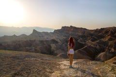 热的太阳是光亮的下来在离开与站立从后面,死亡谷美国的美丽的旅行女孩的超现实的风景的日落前 免版税库存照片