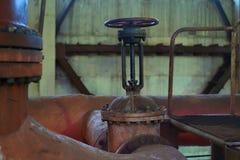 热的工厂与铁管子锅炉和阀门在老状态 免版税库存照片