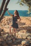 热的性感的时髦的穿戴的小姐深色的头发和带淡红色的摆在淫荡在海sid的面颊与开放腿肩膀和胳膊 免版税库存图片