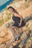热的性感的时髦的穿戴的小姐深色的头发和带淡红色的摆在淫荡在海sid的面颊与开放腿肩膀和胳膊 库存照片