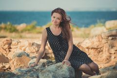 热的性感的时髦的穿戴的小姐深色的头发和带淡红色的摆在淫荡在海sid的面颊与开放腿肩膀和胳膊 免版税图库摄影