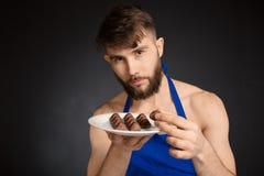 热的性感的赤裸英俊的人用巧克力,巧克力糖 佩带深蓝围裙的微笑的赤裸英俊的人举行白色 库存照片