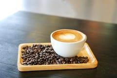 热的拿铁咖啡用在木盘子的咖啡豆 免版税库存照片
