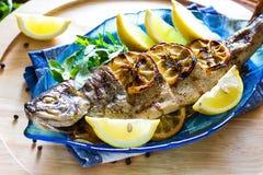 热的新鲜的美味烤整个鳟鱼烤肉用新鲜的草本和柠檬,供食黑胡椒和芝麻菜沙拉在蓝色pla离开 库存图片