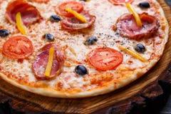 热的新鲜的西西里人的薄饼用烟肉、橄榄和蕃茄服务 库存照片