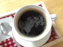 热的无奶咖啡和泡沫在白色杯子和茶匙在红色和白色织品木盘子 免版税库存照片