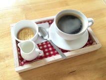 热的无奶咖啡和泡沫在白色杯子和茶匙在红色和白色织品木盘子 免版税库存图片