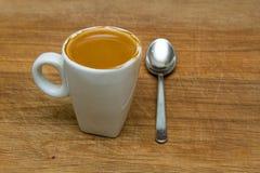 热的杯子在一把木背景和匙子的浓咖啡 免版税库存图片