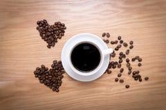 热的杯子由咖啡豆做的浓咖啡和心脏形状在木表面 库存图片
