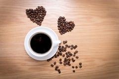 热的杯子由咖啡豆做的浓咖啡和心脏形状在木表面 库存照片