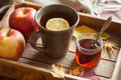 热的柠檬蜂蜜茶温暖的饮料围巾舒适秋叶 免版税图库摄影