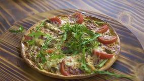 热的比萨用在木桌上的新鲜的草本 原始的意大利比萨用蕃茄、香肠意大利辣味香肠和芝麻菜草本 股票视频