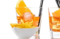 热的炸玉米饼在两块玻璃前面切削喷开胃酒与橙色切片和冰块的aperol鸡尾酒 图库摄影