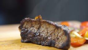 热的烤牛肉BBQ牛排Striploin,菜沙拉和调味汁在切板特写镜头 股票视频