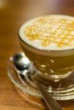 热的焦糖咖啡macchiato和白色牛奶在与s的玻璃起泡沫 免版税库存照片