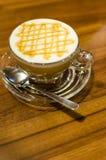 热的焦糖咖啡macchiato和白色牛奶在与s的玻璃起泡沫 图库摄影