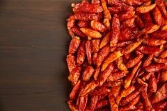 热的红色干胡椒框架在黑褐色木背景的 题字的地方 免版税库存照片