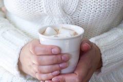 热的自创可可粉用蛋白软糖在妇女的手上 一件白色毛线衣的妇女 土气样式,选择聚焦 免版税库存照片