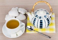 热的茶、茶壶在餐巾和姜饼曲奇饼在桌上 库存图片