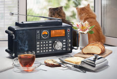 热的茶、面包和油在一张桌上与无线电接收机反对一个开窗口 免版税库存照片