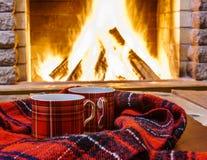 热的茶和舒适温暖的围巾的红色杯子在壁炉附近 免版税库存照片