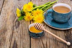 热的茶和芬芳蜂蜜从蒲公英在一个蓝色葡萄酒杯子 免版税库存照片