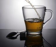 热的茶涌入一个透明杯子 与一份黑暗的饮料的一块美丽的玻璃在集合背景 免版税库存照片
