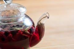 热的茶用在木桌上的莓果 免版税库存照片