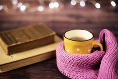 热的茶,热巧克力,在黄色杯子的咖啡,包裹与桃红色编织了围巾 登记老 被弄脏的光,木背景 免版税库存图片