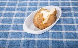 热的蓬松被烘烤的土豆用黄油 免版税库存照片