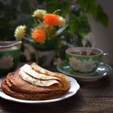 热的薄煎饼用在木桌上的黄油 免版税库存照片