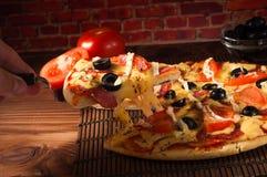 热的薄饼切片用在一张土气木桌上的熔化的乳酪 免版税库存图片
