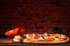 热的薄饼切片用在一张土气木桌上的熔化的乳酪 免版税库存照片