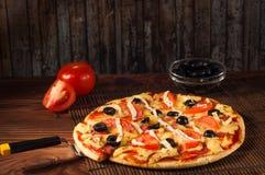 热的薄饼切片用在一张土气木桌上的熔化的乳酪 免版税图库摄影