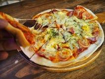 热的薄饼切片用在一张黑暗的木桌上的熔化的乳酪 库存照片