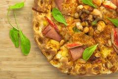 热的薄饼有菠萝、火腿和甜椒顶视图 库存图片