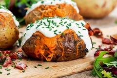 热的被烘烤的土豆用乳酪、烟肉、香葱和酸性稀奶油 免版税库存照片