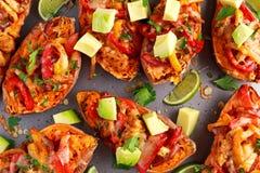 热的被烘烤的白薯充塞用黄色,红辣椒、鸡、乳酪、草本和辣调味汁 所选的重点 库存图片