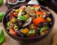 热的辣炖煮的食物茄子、甜椒、橄榄和雀跃 免版税库存照片