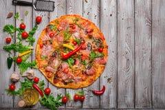 热的辣香肠烘饼一张顶视图在土气桌背景的 与菜和意大利辣味香肠的整个意大利薄饼 复制 免版税库存图片