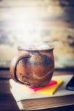 热的饮料、发球区域或者咖啡裁减,在旧书在土气木背景 免版税库存图片