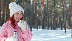 热的饮料冷的冬天,女孩在手上倾吐从金属热水瓶的饮料,热水瓶紧密,手倒茶入杯子 股票视频