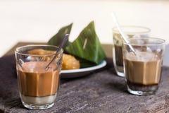 热的饮料泰国牛奶茶,无奶咖啡,可可粉署名地方街道饮料服务用在木桌上的点心 免版税库存照片