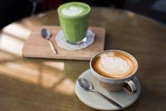 热的饮料用在木桌上的拿铁咖啡matcha绿茶 免版税库存照片