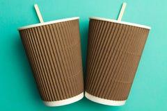 热的饮料的一次性杯子在绿松石背景 纸杯 免版税图库摄影